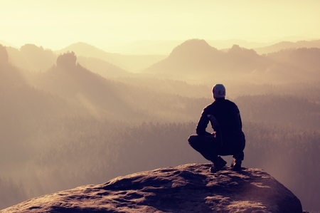 Photo for Young man in black sportswear is sitting on cliff's edge and looking to misty valley bellow - Royalty Free Image