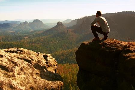 Photo pour High tourist hiker man on the rock peak  in rocky mountains - image libre de droit