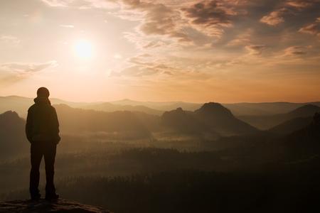 Foto de Sad girl stand on the sharp corner of sandstone rock and watch over valley's Sun. - Imagen libre de derechos