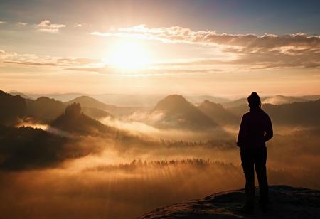 Foto de Alone young girl tourist feast daybreak on the sharp corner of sandstone rock and watch over valley to Sun. - Imagen libre de derechos