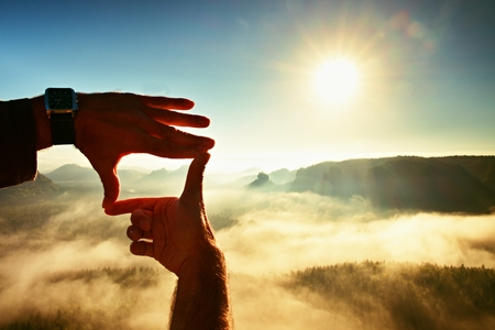 Foto de Close up of hands making frame gesture. Blue misty valley bellow rocky peak. Sunny spring daybreak in mountains. - Imagen libre de derechos