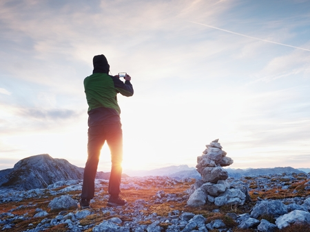 Photo for Alone hiker takes phone photo in mountains. Man on Alps mountain peak.View to purple sky above deep foggy valley. Mountains increased from humidity - Royalty Free Image