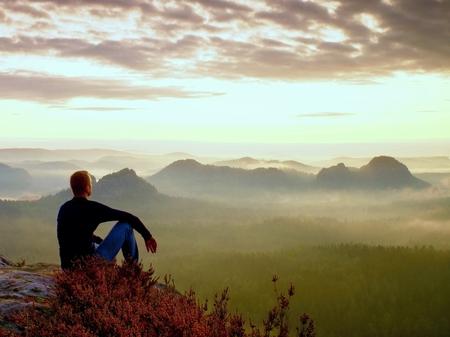 Photo pour Tall hiker in dark shirt sit on a rockatn heather bushes, enjoy foggy  scenery - image libre de droit