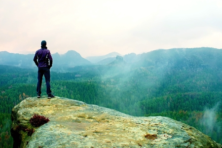 Photo for Man stands on the sandstone rock overlooking the valley to Sun. Beautiful moment - Royalty Free Image
