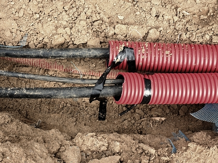 Photo for Excavation of trench  with black cables in protective HDPE tube. Lines of metallic and fiber optic cables, building of communication optical network. The installation of connection. - Royalty Free Image