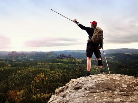 Foto de Happy man hiking holding medicine crutch above head, injured knee fixed in knee brace feature. Scenic mountain top with deep cloudy valley below - Imagen libre de derechos