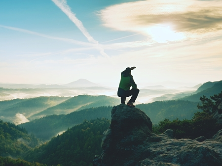 Foto de Hiker man take a rest on mountain peak. Man sit on sharp summit and enjoy spectacular view.  Colorful autumn landscape. Bright morning Sun shining in sky.  - Imagen libre de derechos