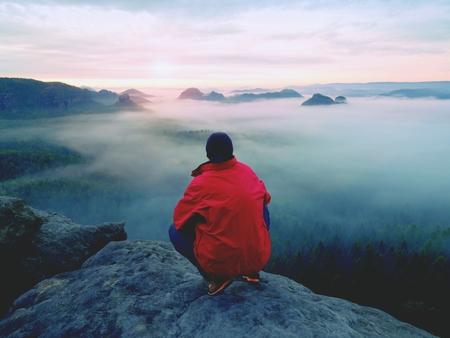 Foto de Man is  staying on a top of a rock above clouds. Man on mountain.  Conceptual design. - Imagen libre de derechos