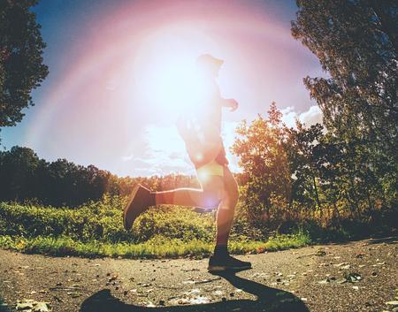 Photo pour The Athletic man running on a forest trail. The man run on a trail in autumn forest - image libre de droit