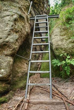 Foto de Ladder stairs climbing in sandstone gulch. Climbers path via ferrata, steel ladder and  rope on a rock - Imagen libre de derechos