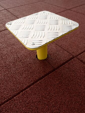 Foto de Outdoor exercising on step platform on red rubbery flexible background.  Safety tile floor made by plastic molding. - Imagen libre de derechos