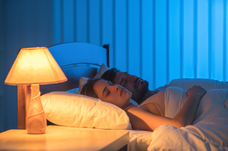 Photo for The man and woman sleeping in the bed. night time, full grip focus - Royalty Free Image
