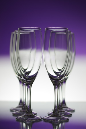 Empty champagne glasses on purple background
