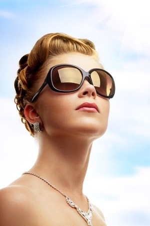 Young woman wearing sunglasses. Sky background
