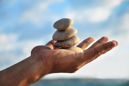 balancing stones in man\'s palm over blue sky