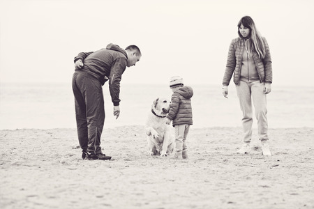 family walking near the sea with dog