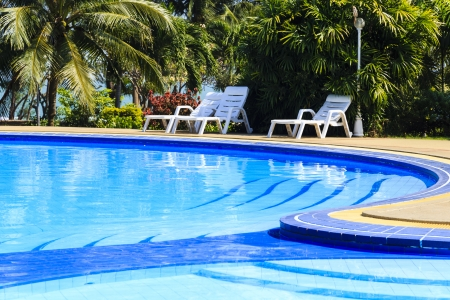 luxury swimming pool with sundeck white close up in tropical garden