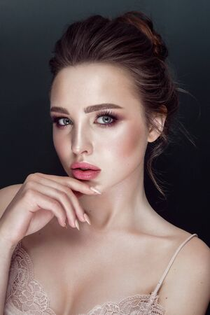 Foto de Glamour portrait of beautiful woman model with fresh daily makeup and romantic wavy hairstyle. Fashion shiny highlighter on skin, sexy gloss lips make-up and dark eyebrows. - Imagen libre de derechos