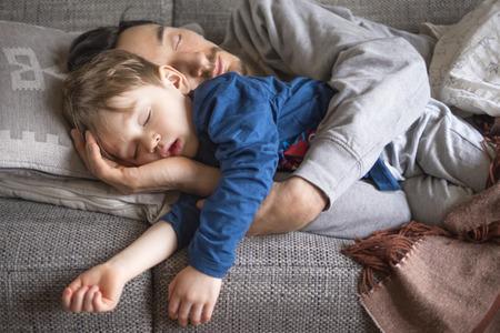 Foto de portrait of father and son fallen asleep together on the couch - Imagen libre de derechos