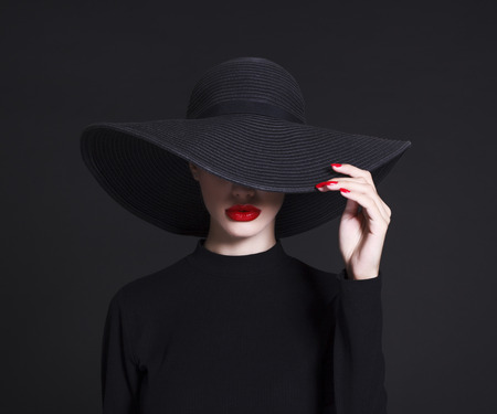 Photo pour Luxury woman in a large black hat and bright lips on black background - image libre de droit