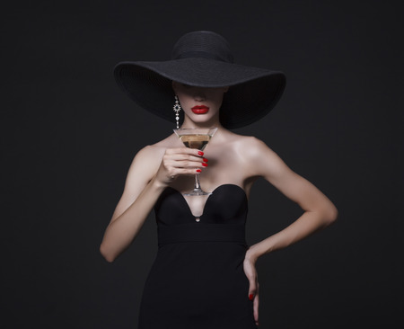 Photo pour Luxury woman in a large black hat and bright lips with a glass of Martini. - image libre de droit
