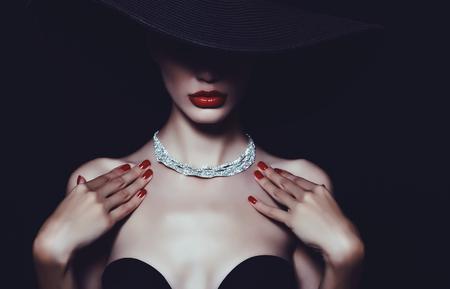 Photo pour A necklace of diamonds on the neck of a luxurious woman in a hat. - image libre de droit