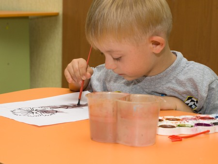 Child with Down syndrome is drawing on a sheet of paper sitting at the table