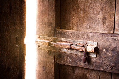Foto de Old dark room with shining closed door. - Imagen libre de derechos