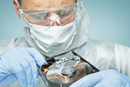 Photo pour Man technician in glasses and gloves is analyzing the hard disk, repair computer - image libre de droit