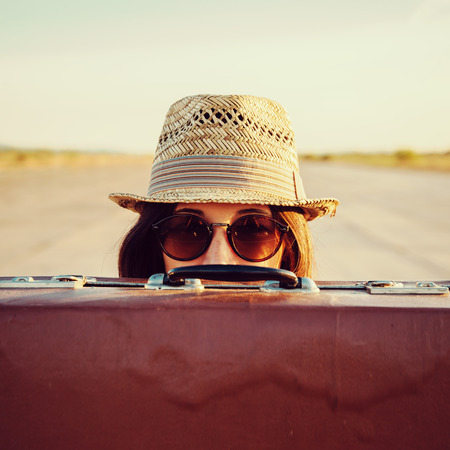 Photo pour Hipster woman in hat and glasses looks out from vintage suitcase - image libre de droit