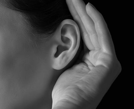 Foto de Unrecognizable woman holds her hand near ear and listens, close-up - Imagen libre de derechos
