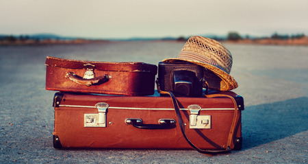 Foto per Vintage suitcases, photo camera and hat on road, concept of travel - Immagine Royalty Free