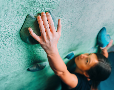Young woman climbing up on wall in gym, focus on hand