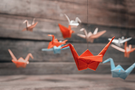 Foto de Colorful many origami paper cranes on wooden background - Imagen libre de derechos