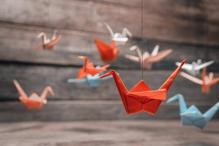Photo pour Colorful many origami paper cranes on wooden background - image libre de droit