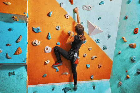 Young woman climbing up on practice wall in gym, rear view