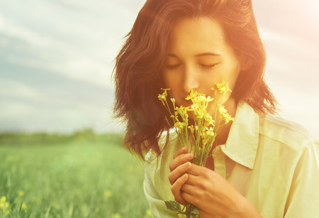 Foto de Beautiful young woman smelling yellow flowers with closed eyes in summer outdoor. Image with sunlight effect - Imagen libre de derechos