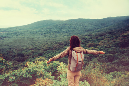 Foto de Freedom traveler woman standing with raised arms and enjoying a beautiful nature. Image with instagram filter - Imagen libre de derechos