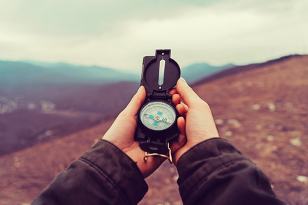 Photo for Hiker woman searching direction with a compass in the mountains. Point of view shot - Royalty Free Image