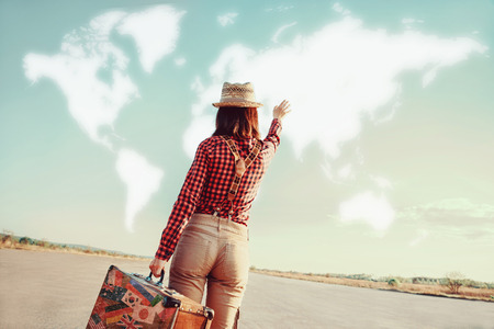 Photo for Traveler woman with vintage suitcase waves her hand to map of the world. Concept of travel - Royalty Free Image