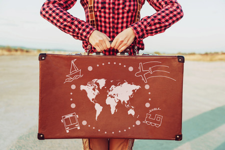 Photo pour Traveler woman standing with a suitcase. Map of the world and types of transport are painted on suitcase. Concept of travel - image libre de droit