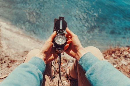 Photo for Traveler woman searching direction with a compass on coastline near the sea. Point of view shot - Royalty Free Image