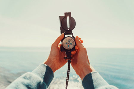 Photo pour Traveler woman searching direction with a compass on background of sea. Point of view shot - image libre de droit