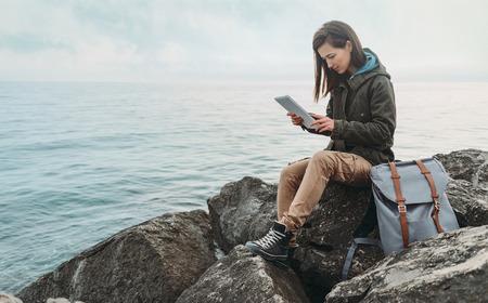 Foto de Traveler girl sitting on coast near the sea and working on digital tablet - Imagen libre de derechos