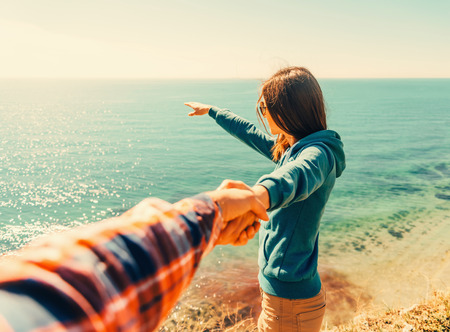 Couple in love. Beautiful young woman holding man's hand and showing him something in distance the sea.