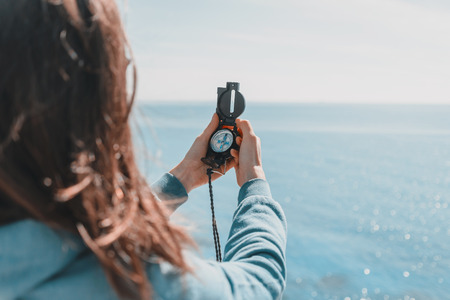 Photo for Traveler woman searching direction with a compass on coastline near the sea in summer - Royalty Free Image