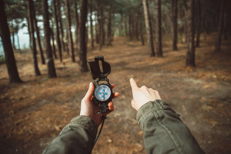 Photo pour Traveler woman holding a compass and pointing direction in the forest. Close-up. Point of view shot - image libre de droit