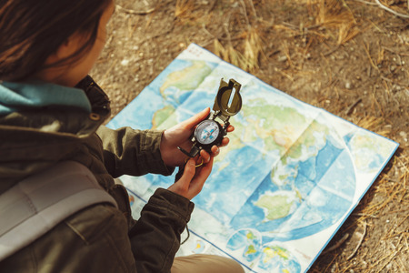 Photo for Traveler young woman searching direction with a compass on background of map in the forest - Royalty Free Image