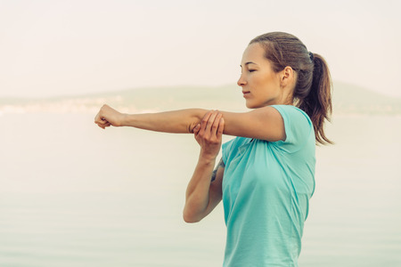 Foto per Young woman stretching her arms on beach in summer in the morning. Concept of healthy lifestyle - Immagine Royalty Free