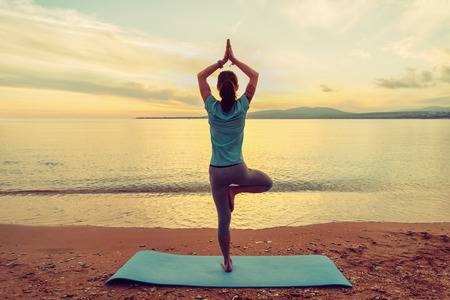 Foto de Young woman doing yoga exercise in pose of tree on beach at sunset in summer, rear view - Imagen libre de derechos